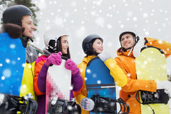 Happy friends in helmets with snowboards talking Royalty Free Stock Photo
