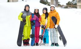 Happy friends in helmets with snowboards Stock Image