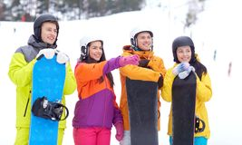 Happy friends in helmets with snowboards Royalty Free Stock Image