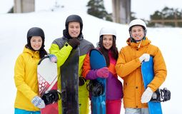 Happy friends in helmets with snowboards. Winter, leisure, extreme sport, friendship and people concept - happy friends in helmets with snowboards Stock Photos