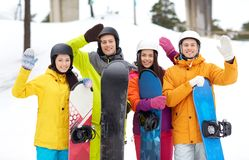 Happy friends in helmets with snowboards Royalty Free Stock Images