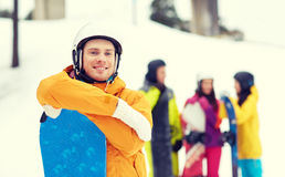 Happy friends in helmets with snowboards Stock Photo