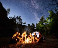 Friends hikers resting beside camp, campfire, tent at night royalty free stock images