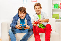Happy friends hold joysticks and play game console royalty free stock image