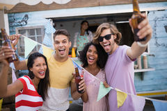 Happy friends holding beer bottles. Near food truck Royalty Free Stock Photo