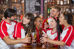 Happy friends holding beer bottles. In pub Stock Images