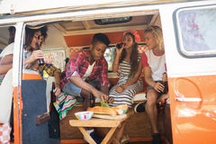 Happy friends holding beer bottles while sitting in camper van Royalty Free Stock Photos