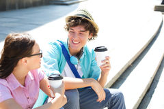 Happy friends holding disposable coffee cups while sitting on steps outdoors Royalty Free Stock Photography