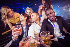 Happy friends holding a glass of alcohol Royalty Free Stock Images