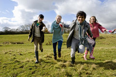 Happy friends holding hands and running in sunny, rural field royalty free stock photos