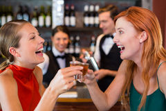 Happy friends holding a tequila shot in front of bar counter Stock Photos
