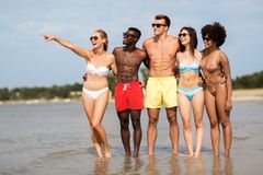 Happy friends hugging on summer beach royalty free stock images
