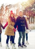 Happy friends ice skating on rink outdoors Stock Images