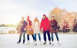 Happy friends ice skating on rink outdoors. People, winter, friendship, sport and leisure concept - happy friends ice skating on rink outdoors royalty free stock photography