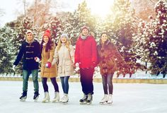 Happy friends ice skating on rink outdoors. People, winter, friendship, sport and leisure concept - happy friends ice skating on rink outdoors stock photo