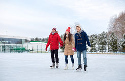 Happy friends ice skating on rink outdoors Stock Photos