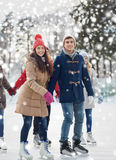 Happy friends ice skating on rink outdoors Stock Photo