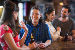 Happy friends interacting at bar counter. In pub Stock Photos