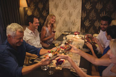 Happy friends interacting with each other while having dinner Stock Photos