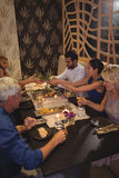 Happy friends interacting with each other while having dinner Stock Images