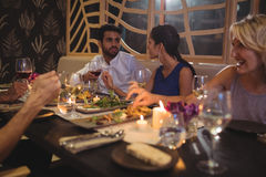 Happy friends interacting with each other while having dinner. In restaurant Royalty Free Stock Photo
