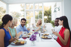 Happy friends interacting with each other while having meal Royalty Free Stock Image