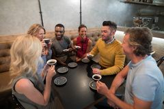 Happy friends interacting while having coffee. At cafe Royalty Free Stock Image