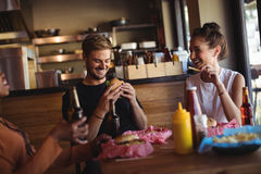 Happy friends interacting while having meal and beer. In restaurant Stock Photography