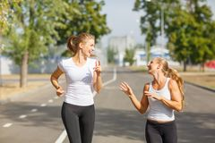 Happy friends jogging on a blurred background. Happy girl runners. Activity concept. Copy space. Stock Photography