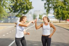 Happy friends jogging on a blurred background. Happy girl runners. Activity concept. Copy space. Stock Photos