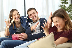 Happy friends joking throwing popcorn. Three happy friends joking and throwing popcorn sitting on a sofa in the living room at home Stock Images