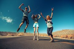 Happy friends jump and have fun. On an asphalt road in a desert. Tilt shift effect applied stock images