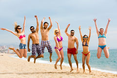 Happy friends jumping on beach Royalty Free Stock Photo