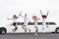Happy friends jumping in front of a limousine Stock Photo