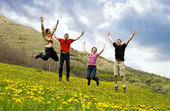 Happy friends jumping in meadow Stock Photos