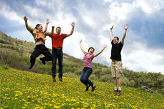 Happy friends jumping in meadow. Happy friends jumping in dandelion field Royalty Free Stock Images