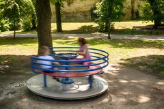 Happy friends, kids having fun on roundabout at playground . stock photos