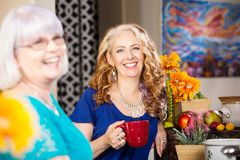 Happy Friends in Kitchen drinking from mugs royalty free stock photo