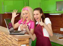 Happy friends on kitchen with a laptop Royalty Free Stock Photo