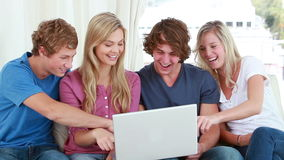 Happy friends laughing in front of a laptop Royalty Free Stock Photography