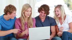 Happy friends laughing while looking at a laptop Stock Images