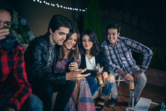 Happy friends laughing and looking smartphone in party. Group of happy young friends drinking and laughing while looking a smartphone picture in a outdoors party Stock Image