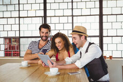 Happy friends laughing while looking at tablet Stock Images