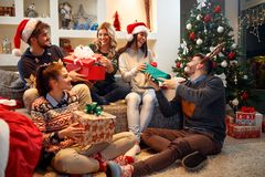 Happy friends laughing and sharing Christmas gifts Royalty Free Stock Photography