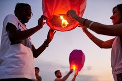 Happy friends launching sky lanterns stock photography