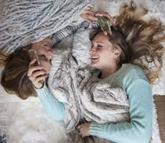 Happy friends laying on blankets with phones laughing Royalty Free Stock Image