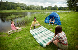 Happy friends laying picnic blanket at campsite. Camping, travel, tourism, hike and people concept - happy friends with tent laying picnic blanket at campsite on Stock Photography