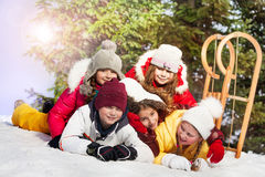Happy friends laying at the snow in winter forest Royalty Free Stock Image