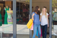 Happy friends leaving out a clothing store Stock Photo