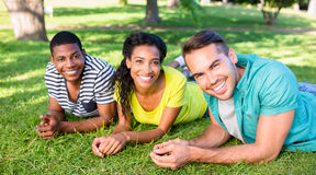 Happy friends lying on campus. Portrait of happy friends lying on grass at college campus Royalty Free Stock Photo